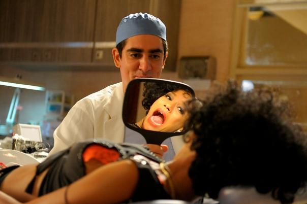 Paladino (Marcelo Adnet) segurando um espelho na frente de Sheila (Taís Araújo) que vê o resultado do tratamento. - Crédito: TV Globo/Estevam Avellar